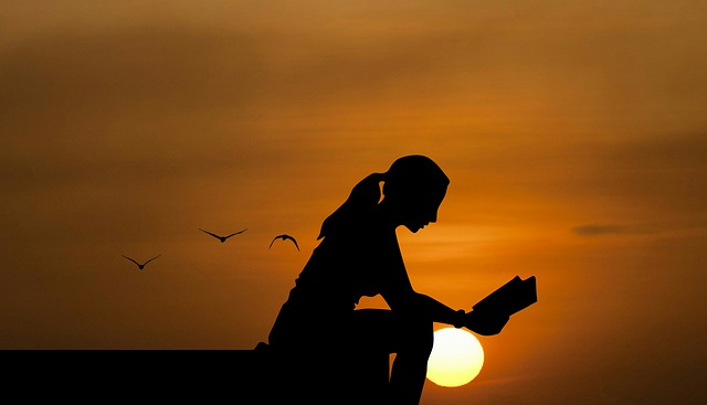 girl silhouette reading a book at sunset